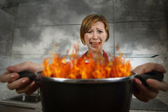 Young inexperienced home cook woman in panic with apron holding pot burning in flames with in panic Stock Photography