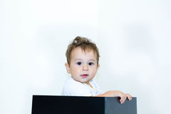 A young infant boy peeking out of a box on a white background Stock Images