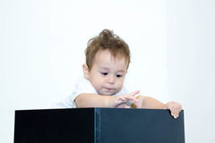 A young infant boy peeking out of a box on a white background Royalty Free Stock Photos