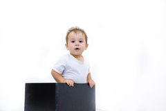 A young infant boy peeking out of a box on a white background Royalty Free Stock Photography