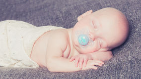 A young infant sleeping. A newborn boy sleeping peacefully on a blanket with a smile on his face stock photos