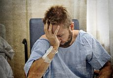 Young injured man in hospital room sitting alone in pain worried for his health condition. Young injured man crying in hospital room sitting alone in pain royalty free stock photography