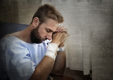 Young injured man in hospital room sitting alone in pain worried for his health condition Royalty Free Stock Image