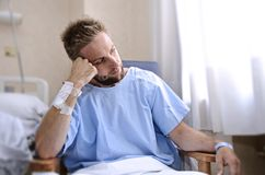 Young injured man in hospital room sitting alone in pain worried for his health condition Stock Photography