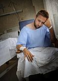 Young injured man in hospital room sitting alone in pain worried for his health condition Stock Photo