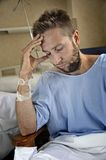 Young injured man in hospital room sitting alone in pain worried for his health condition. Young injured man in hospital room sitting alone in pain looking stock photography