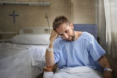 Young injured man in hospital room sitting alone in pain worried for his health condition Royalty Free Stock Photography