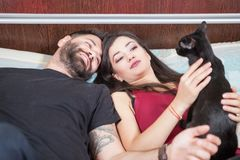 Young inlove couple on the bed with their cats Royalty Free Stock Photo