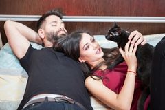 Young inlove couple on the bed with their cats Stock Photos