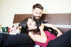 Young inlove couple on the bed with their cats Royalty Free Stock Images