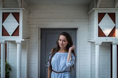 Young inscrutable woman stands at the entrance. Of a colonial style wooden white house. Beautiful girl in light dress on the background of old stylish building Royalty Free Stock Image