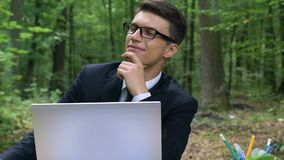 Young inspired businessman working in forest, abstracting mind from troubles stock video footage