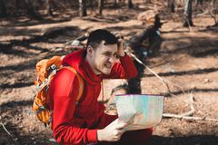 Man with backpack reading map in woods stock photos