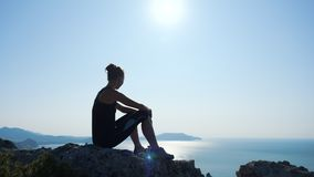 Young inspired woman sitting on the top of a mountain above the sea against beautiful blue sky. Silhouette of a happy