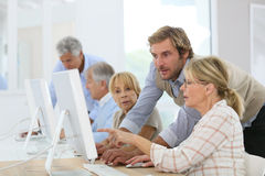 Young instructor assisting seniors in computing class Royalty Free Stock Image