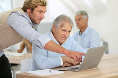 Young instructor helping senior man in class Stock Photos