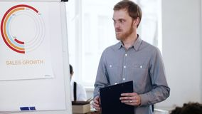 Young intelligent Caucasian businessman leading office seminar meeting, presenting sales diagram on flipchart. Professional focused male finance expert stock video