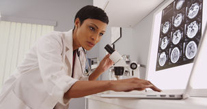 Young intelligent female radiologist looking in a microscope Stock Photos