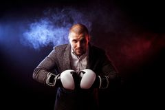 Man businessman in gray suit and boxing gloves stock photography