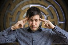 Young intelligent man is thinking and solving difficult task Royalty Free Stock Image