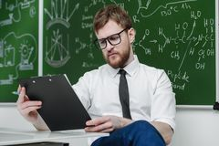 Educated intelligent teacher. Young intelligent teacher conducts a chemistry lesson. Educational concept stock photo