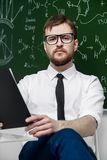 Well-educated young professor. Young intelligent teacher conducts a chemistry lesson. Educational concept royalty free stock images