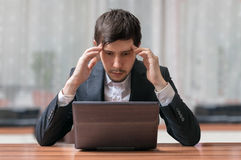Young intend and thinking businessman working with laptop.  Royalty Free Stock Images