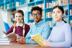 Preparing for exam. Young intercultural college students in casualwear looking at camera while preparing for seminar or exam together Stock Photo