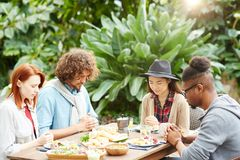 Blessing food. Young intercultural guys and girls saying pray by table before having dinner Stock Photo