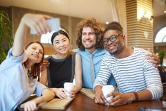 Selfie at break. Young intercultural students or managers making selfie in cafe while sitting by table at coffee-break Royalty Free Stock Photo