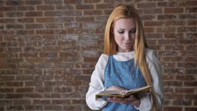 Young interested blonde girl is reading book, watching at camera, smiling, brick background.  stock footage