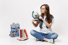 Young interested smart woman student keeping finger on world globe learning about countries sitting near backpack school stock photo