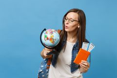 Young interested woman student in glasses looking on world glove holding passport, boarding pass tickets isolated on. Blue background. Education in university royalty free stock photography