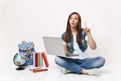 Young interested woman student holding laptop pc computer pointing index finger up sitting near globe, backpack, school. Books isolated on white background stock image