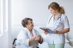 Young doctor with pad and stethoscope and elderly grandmother with cane stock images