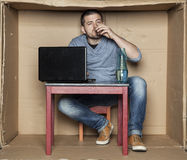 Young intern drink a glass of alcohol at work Royalty Free Stock Images