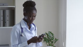 Young intern in hospital messaging on smartphone.