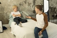 Young international gay couple in quarrel at home in bedroom stock image