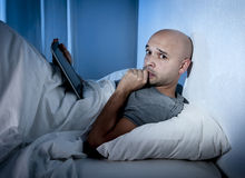 Young internet addict man awake at night in bed using digital pad or tablet Stock Photos