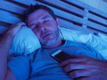 Young internet addict man sleeping on bed holding mobile phone in his hand at night in smartphone and social media network overuse. Lifestyle indoors portrait of royalty free stock photos