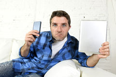 Young internet and technology addict man networking with mobile phone and digital tablet. Young internet and technology addict man at home couch networking with Stock Photos
