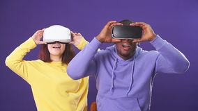 Young interracial couple having first experience of using virtual reality headset. Standing joyful and impressed in studio with violet background stock footage