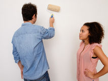 Young interracial couple painting the house wall together Royalty Free Stock Photos