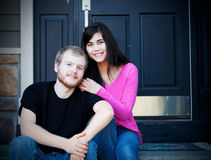Young interracial couple sitting on front steps. Happy young interracial couple sitting on front steps of home Stock Images