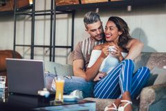 Young interracial couple spending time in cafe. Watching media together on laptop royalty free stock photography