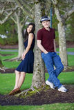 Young interracial couple standing by tree stock image
