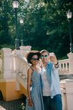 young interracial couple in sunglasses taking selfie on smartphone stock photography