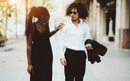 A young interracial couple, talking on a sidewalk royalty free stock photo
