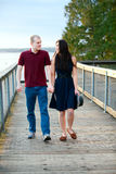 Young interracial couple walking together on wooden pier over la. Young happy interracial couple walking together on wooden pier over lake Royalty Free Stock Image