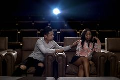 Interracial couple on a movie theater date. Young interracial dating couple in a movie theater watching a show.  The men is asian and the women is black.  They Stock Photo